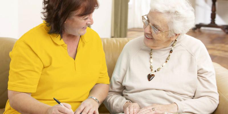 Mitarbeiterin im Gespräch mit einer Seniorin