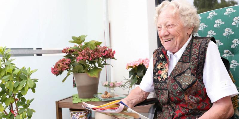 Lachende Seniorin auf dem Balkon