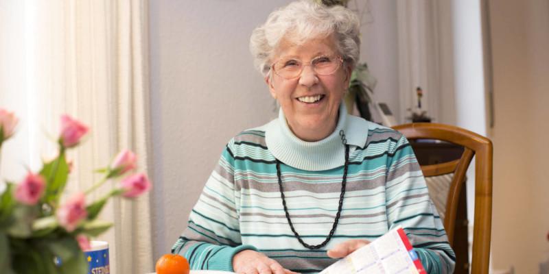 Lachende Seniorin blättert in einer Zeitschrift