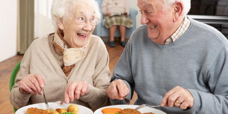 Lächelnde Senioren am Esstisch