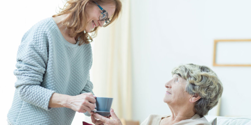 Jüngere Frau reicht einer älteren Dame eine Tasse Tee
